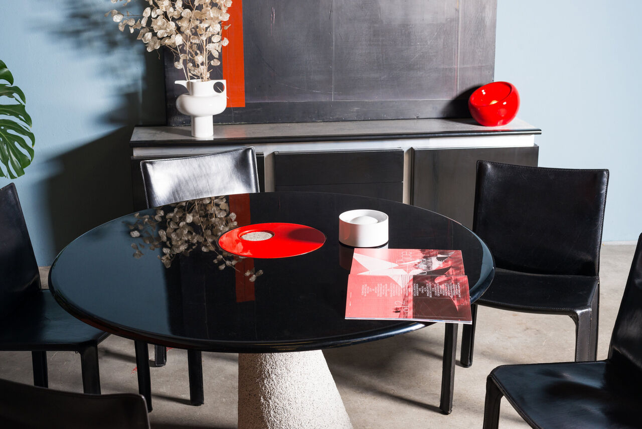 Concrete base dining table with black and red lacquer top